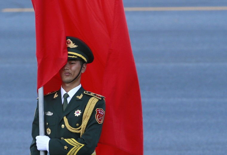A Chinese honor guard holds a red flag during an official welcoming ceremony for Malaysia's King Abdul Halim at the Great Hall of the People in Beijing, September 4, 2014. (Kim Kyung-Hoon/Reuters)