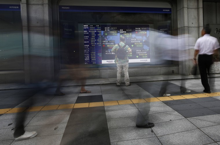 A man looks at an electronic board displaying stock prices, including Japan's Nikkei average (top C), as passers-by walk past outside a brokerage in Tokyo September 4, 2014. Japanese stocks fell on Thursday, snapping a three-day winning streak as most investors took profits from the recent gains after they quickly priced in the Bank of Japan's decision to maintain its massive monetary stimulus and its upbeat view on the economy. Picture taken with a long exposure. (Issei Kato/Reuters)