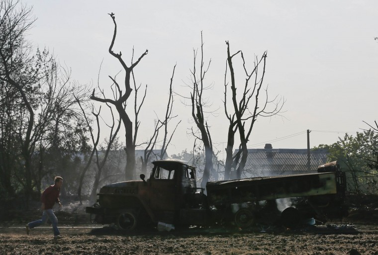 A man runs past a burnt truck belonging to Ukrainian forces near the village of Berezove, southwest from Donetsk, September 4, 2014. (Maxim Shemetov/Reuters)