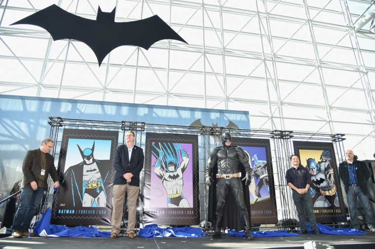(L-R) Greg Breeding, Art Director of USPS, Jim Cochrane, Chief Information Officer and Executive Vice President of USPS, a model dressed as Batman, Jim Lee, Co-Publisher of DC Entertainment, and Dan DiDio, Co-Publisher of DC Entertainment unveil the USPS Batman Forever stamp at the launch of the stamp series at Jacob Javitz Center on October 9, 2014 in New York City. Mike Coppola/Getty Images