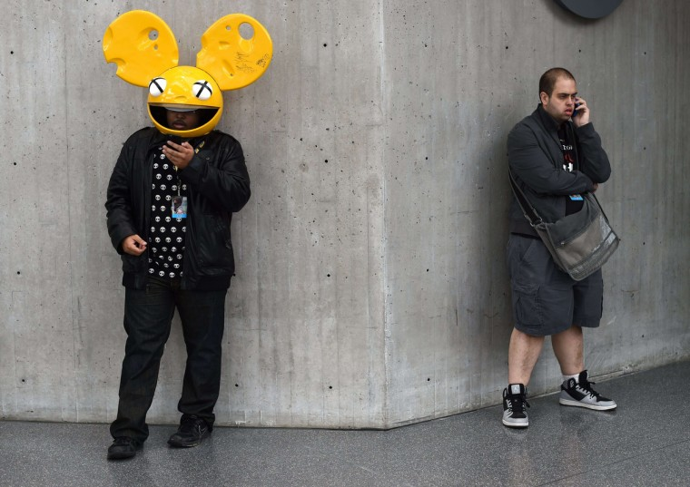 Fans in costume talk on cell phones at the opening session of the 2014 New York Comic Con at the Jacob Javits Center. Timothy A. Clary/AFP/Getty Images