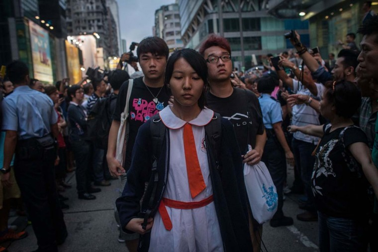 Students and pro-democracy activists leave the protest site as local police hold back local residents and pro-government supporters on October 3 in Mong Kok, Hong Kong. Fights broke out between local residents and pro government supporters when they attempted to force pro-democracy activists from their protest site. Thousands of pro democracy supporters continue to occupy the streets surrounding Hong Kong's Financial district. Protest leaders have set an October 1st deadline for their demands to be met and are calling  for open elections and the resignation of Hong Kong's Chief Executive Leung Chun-ying.  ||Photo by Chris McGrath/Getty Images