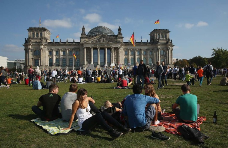 People relay on the lawn infront of the Reichstag on German Unity Day (Tag der Deutschen Einheit) on October 3 in Berlin, Germany. Germany is celebrating the 24th anniversary of the day when former West Germany and East Germany reunited into modern Germany in 1990 following the end of the Cold War. As the now-unified Germany prepares to celebrate 25 years since the days of the Berlin Wall and the infamous Stasi, the federal government there continues to be wary of U.S. spying and surveillance practices.  ||Photo by Sean Gallup/Getty Images