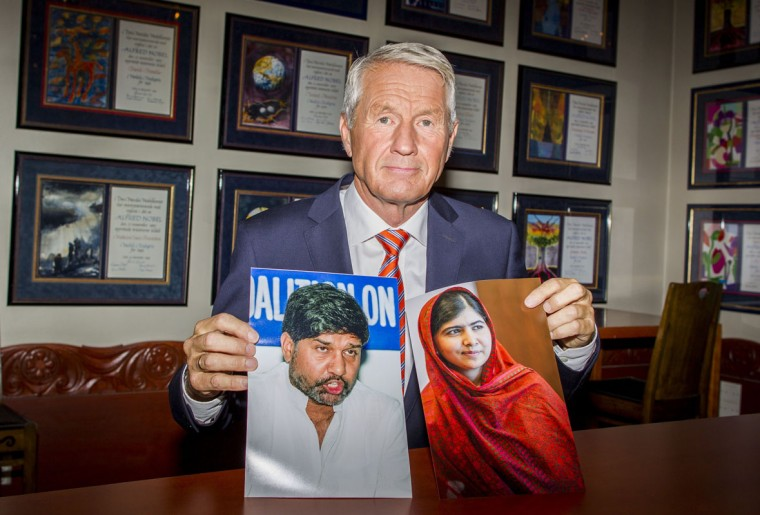The chairman of the Norwegian Nobel Committee, Thorbjorn Jagland, poses with pictures of Pakistani education activist Malala Yousafzai (R) and Kailash Satyarthi (L), Indian anti-child labour activist, who have been awarded the Nobel Peace Prize 2014 at the Nobel Institute in Oslo on October 10, 2014. (Vegard Wivestand Grott/AFP/Getty Images)