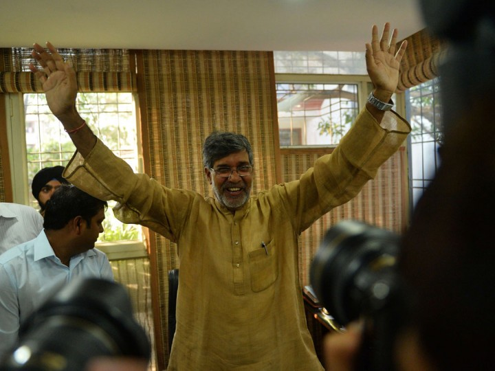 Indian activist Kailash Satyarthi gestures for photographers at this home office after the announcement of him receiving the Nobel Peace Prize, in New Delhi on October 10, 2014. Indian activist Kailash Satyarthi said October 10 his Nobel Peace Prize would help highlight the plight of children around the world, and invited fellow winner Malala Yousafzai to work with him. (Khanna Chadan/AFP/Getty Images)