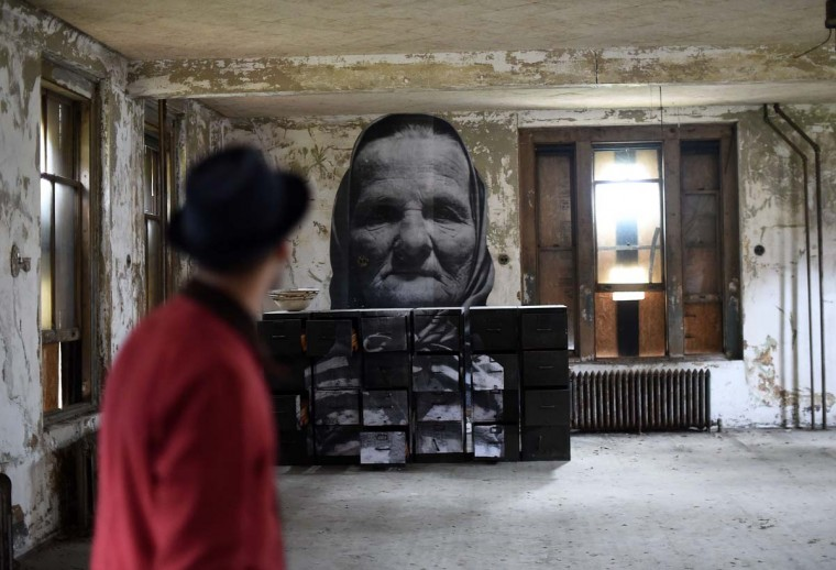 French street artist JR explains his art works to journalists inside the Ellis Island Immigrant Hospital during a media tour in New York on October 16. The abandoned 1902 hospital on New York's Ellis Island now has a photographic installation by the artist. Century-old black-and-white photographs were enlarged to life-size proportions, and then pasted on walls, windows and other corners of the derelict hospital, which is now open to the public for the first time in 60 years.  || CREDIT: JEWEL SAMAD - AFP/GETTY IMAGES