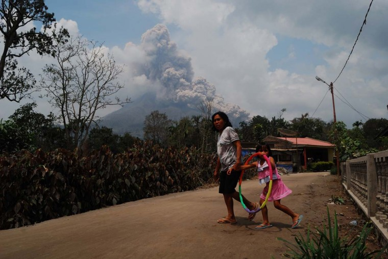 In this photograph taken on October 16, 2014, a woman and a child is seen in a village while Mount Sinabung volcano erupts in the background as seen from Karo district on Sumatra island. In February, Sinabung's eruption killed about 17 people and forced more than 33,000 others to flee their homes.   || CREDIT: SUTANTA ADITYA - AFP/GETTY IMAGES