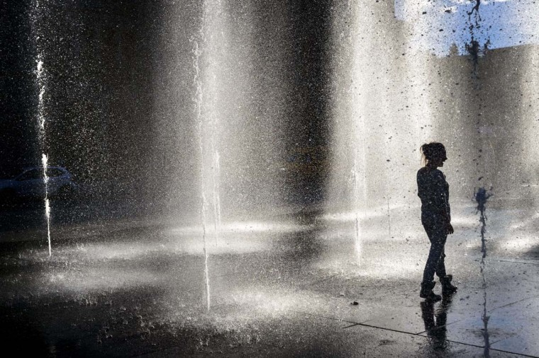 A women walks in a middle of the Federal square fountain on October 17 in the Swiss capital Bern during the end of a warm autumn day.   || CREDIT: FABRICE COFFRINI - AFP/GETTY IMAGES