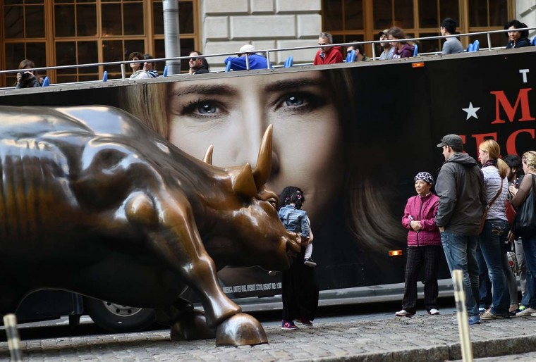 Tourists have their picture taken with the Charging Bull, which is sometimes referred to as the Wall Street Bull, in New York on October 17.   || CREDIT: JEWEL SAMAD - AFP/GETTY IMAGES