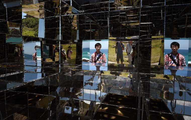"A man looks into a mirrored sculpture by artist Neon titled ""House of mirrors"" overlooking Sydney's coastline as artists from 16 countries prepare their works for the upcoming Sculpture by the Sea exhibition (William West/AFP/Getty Images)"