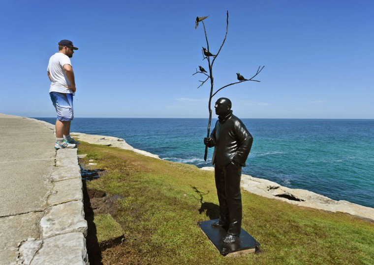 "A man looks at a sculpture by artist Wang Shugang of China titled ""man playing with birds"" overlooking Sydney's coastline as artists from 16 countries prepare their works for the upcoming Sculpture by the Sea exhibition, on October 23, 2014. (William West/AFP/Getty Images)"