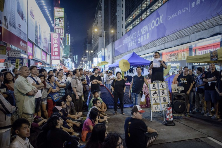 People listen to an improvised public debate held by pro-democracy protesters at a protest site in the Mongkok district of Hong Kong on October 27, 2014. Four weeks after tens of thousands of Hong Kongers took to the streets demanding free leadership elections for the semi-autonomous Chinese city, weary demonstrators remain encamped across several major roads. (Philippe Lopez/AFP/Getty Images)