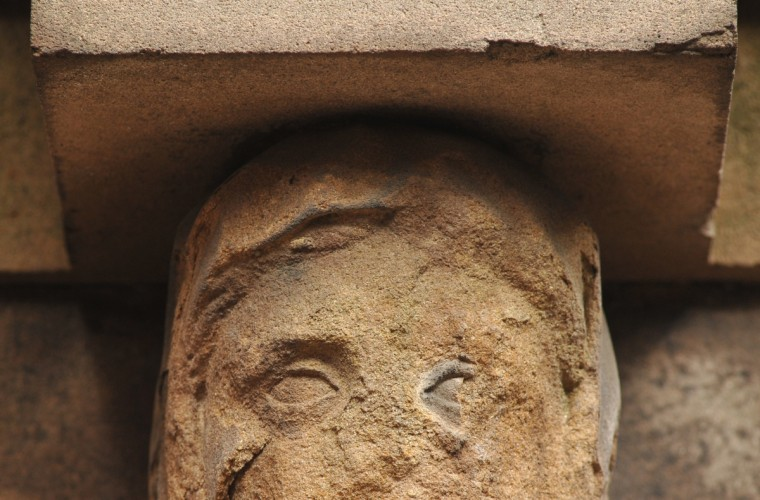 The eyes on a badly weathered sandstone head, one of two on the O'Donnell vault, still show an Egyptian influence in the design by French architect Maximilian Godefroy. Amy Davis / Baltimore Sun