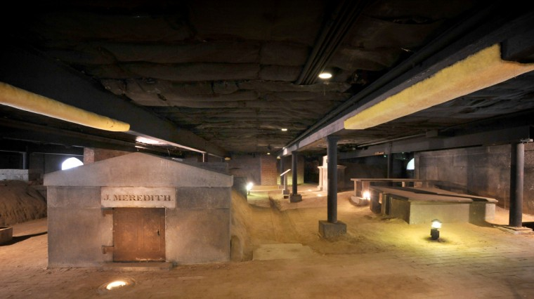 Looking north toward Fayette Street from the south end of the catacombs. At left is the burial vault for the Jonathan Meredith family. The low beams above passageways are covered with carpeting to avoid painful bumps to the head. Amy Davis / Baltimore Sun