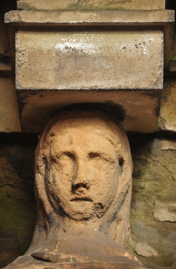 One of two worn sandstone female heads on the O'Donnell vault, atop columns supporting the entablature. Amy Davis / Baltimore Sun