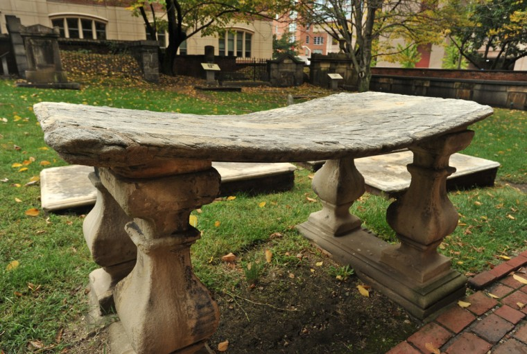 The curvature of this raised slab, originally part of a lot belonging to William Matthews, a merchant who served in the Revolutionary War, shows how the elements and pollution erode the stone tablets. Amy Davis / Baltimore Sun
