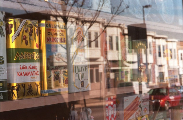 12/17/97: The north side of the 4700 block of Eastern Ave. is reflected in the display window of the Greek Town Bakery and Delicatessen stocked with a panoply of olive oils. (Jed Kirschbaum/Sun staff)