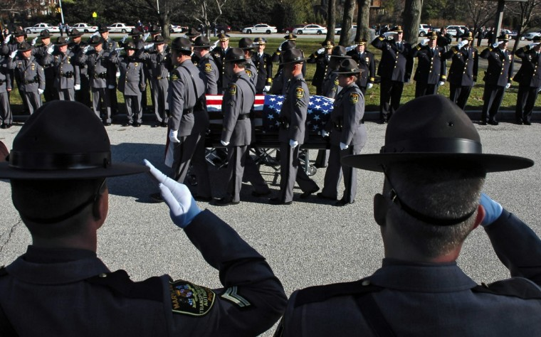 Funeral services at Cathedral of Mary Our Queen are held for Maryland Transportation Authority police officer Courtney G. Brooks, who died New Year's Day after being struck by a vehicle. MTA police officers, foreground, and from other jurisdictions salute as the flag draped coffin carrying Cpl. Brooks passes by after the memorial service. (Kenneth K. Lam/Baltimore Sun)