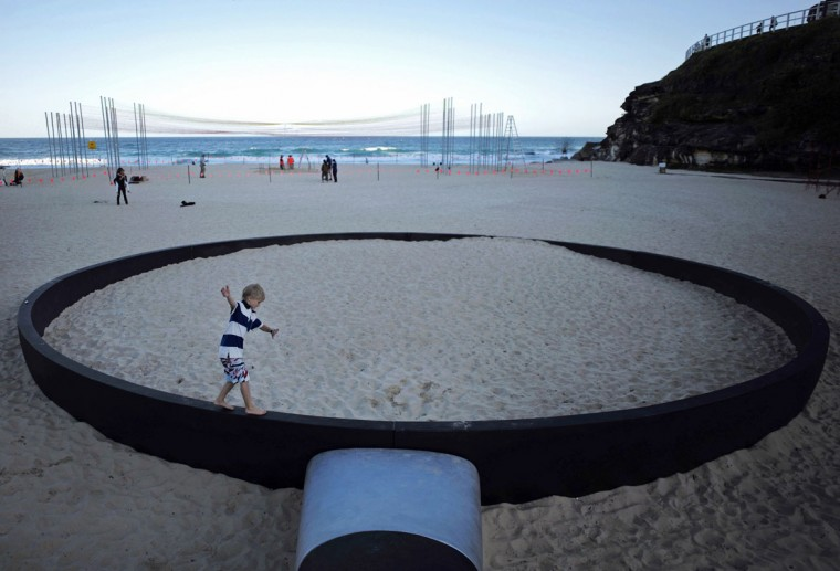 "A boy runs along the rim of a giant frying pan sculpture by Andrew Hankin titled 'We're frying out here' as part of the ""Sculpture by the Sea"" exhibition at Sydney's Tamarama Beach. (Jason Reed/Reuters)"