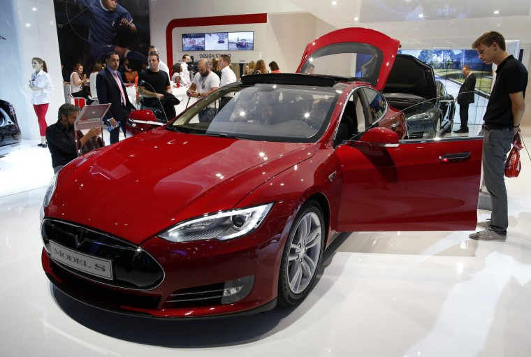 Visitors look at a Tesla Model S car displayed on media day at the Paris Mondial de l'Automobile, October 2, 2014. The Paris auto show opens its doors to the public from October 4 to October 19. Benoit Tessier/Reuters photo