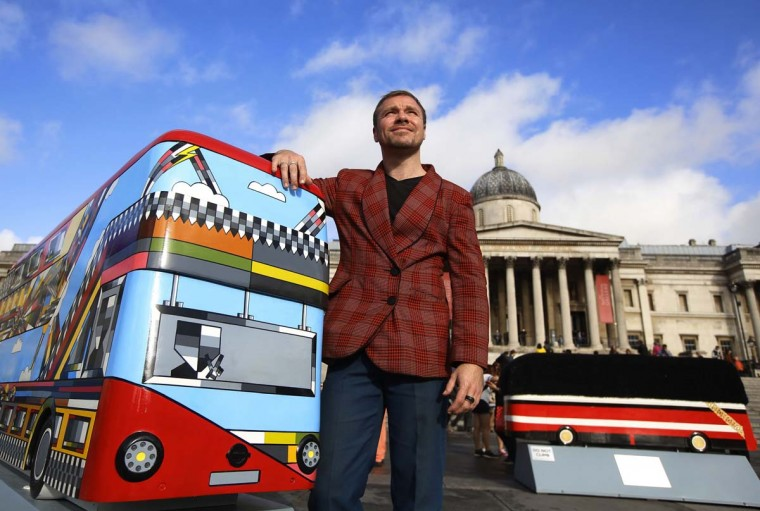 "Artist Thomas W. Dowdeswell poses with his new Routemaster bus sculpture entitled ""Come Rain or Come Shine"" at Trafalgar Square in London October 17. The sculpture forms part of a collection of 60 bus sculptures decorated by artists that will be placed across the capital to create walking trails, before being auctioned for charity in 2015.   