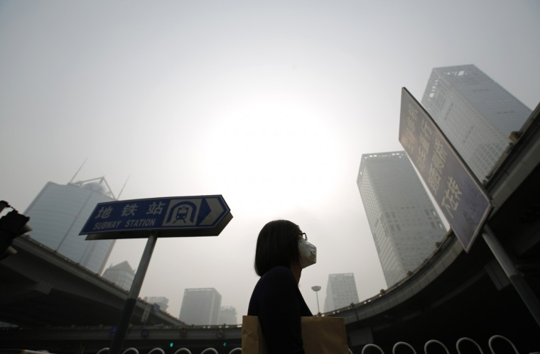 A woman wearing a mask makes her way on a street amid heavy haze and smog in Beijing, in this October 11, 2014 file picture. China's capital is expected to face more heavy smog from October 29, 2014 as it battles to try to guarantee air quality ahead of an Asia-Pacific Economic Cooperation (APEC) summit starting on Saturday, forecasters said. Beijing and nearby regions will impose their most stringent pollution controls since the 2008 Summer Olympics as they bid to maintain air quality during the summit, which will be attended by U.S. President Barack Obama and other world leaders. (Kim Kyung-Hoon/Reuters)