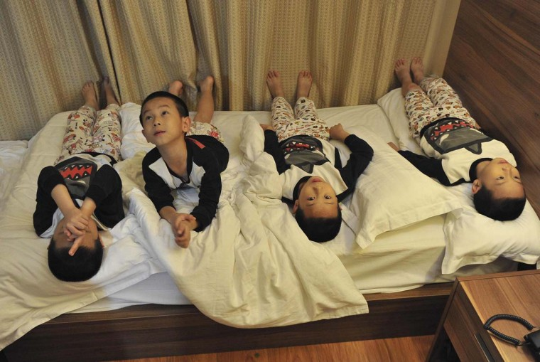 Eight-year-old quadruplets Jiang Yunlong, Yunxiao, Yunhan and Yunlin lie on a bed at a hotel after they attended a show in Beijing October 15. Tan Chaoyun, mother of the Jiang brothers, gave birth to the boys at the age of 41 in Shenzhen, according to local media. || PHOTO CREDIT: STRINGER  - REUTERS