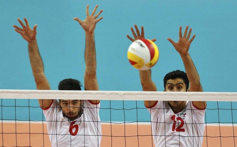 Iran's Seyed Mohammad Mousavi Eraghi (L) and Mojtaba Mirzajanpourmouziraji defend during their men's gold medal volleyball match against Japan at Songnim Gymnasium during the 17th Asian Games in Incheon October 3.  || PHOTO CREDIT: OLIVIA HARRIS  - REUTERS