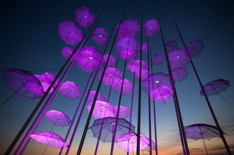 """""""Umbrellas"""", the sculpture by Giorgos Zogolopoulos is illuminated in pink light to mark Breast Cancer Awareness Month in Thessaloniki in northern Greece October 21, 2014. (REUTERS/Alexandros Avramidis)"""