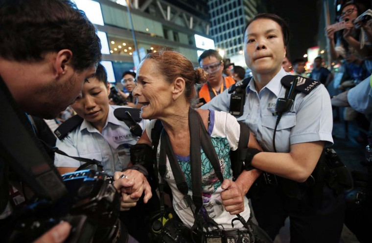 Police officers detain Getty Images photographer Paula Bronstein during a confrontation between police and pro-democracy protesters at Mongkok shopping district in Hong Kong October 17. Hong Kong riot police used pepper spray and baton charged pro-democracy protesters who mobilised en masse on Friday evening after a pre-dawn clearance of a major protest zone in the Chinese-controlled financial hub.  || PHOTO CREDIT: CARLOS BARRIA  - REUTERS