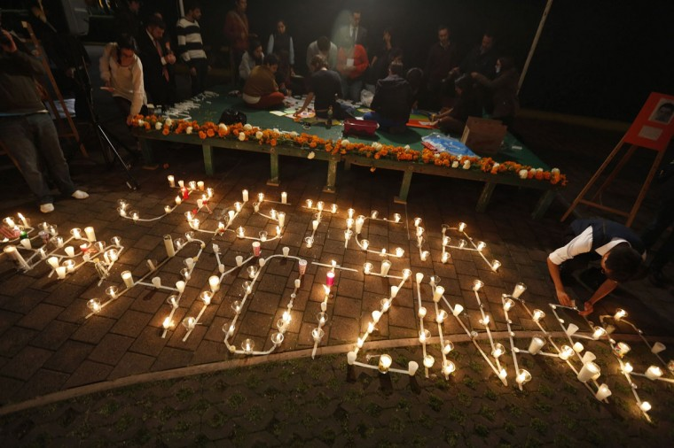 """Students at the Instituto Tecnologico Autonomo de Mexico (ITAM) in Mexico City arrange candles to form the words """"Justice for Ayotzinapa"""" during a vigil for 43 Ayotzinapa students missing after last month's deadly clashes, October 14, 2014. On September 26, police allegedly linked to a criminal gang shot dead at least three students and abducted dozens of others during clashes in the southwestern city of Iguala. Forty-three of the students are still missing. (REUTERS/Tomas Bravo)"""