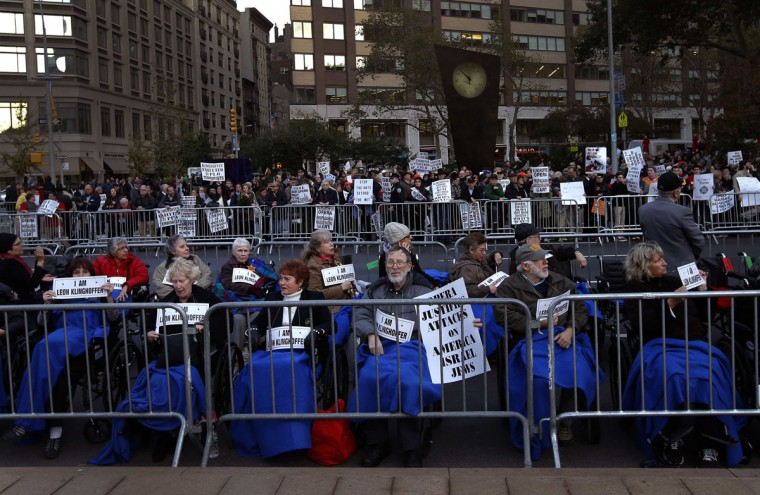 """Protesters sit in wheelchairs during a demonstration across from Lincoln Center and the New York Metropolitan Opera in New York, October 20, 2014. New York's Metropolitan Opera was bracing for its most tumultuous opening in decades on Monday as protestors demonstrated against """"The Death of Klinghoffer,"""" the John Adams opera about the 1985 hijacking of a cruise ship by Palestinian guerillas. The opera, seen by some as a humanist masterpiece and by others as anti-Semitic, depicts the murder of Leon Klinghoffer, a Jewish man on a cruise with his wife aboard the Achille Lauro. After his death, the killers threw the body of the retired New Yorker overboard along with his wheelchair. (REUTERS/Mike Segar)"""