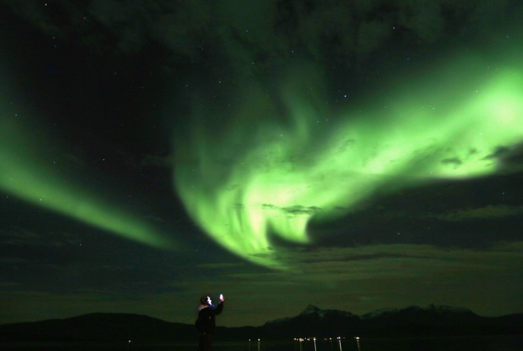 A tourist takes photos of an Aurora Borealis (Northern Lights) over the Bals-Fiord north of the Arctic Circle, near the village of Mestervik late September 30, 2014. (Yannis Behrakis/Reuters)