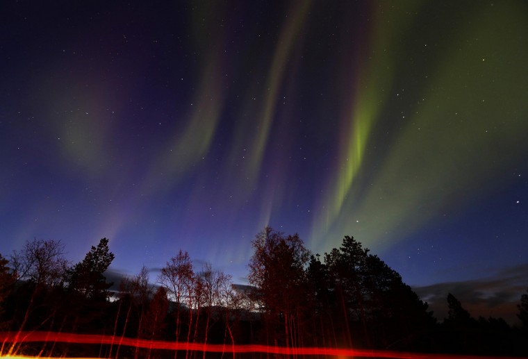 Vehicles drive by as a display of Aurora Borealis (Northern Lights) is seen north of the Arctic Circle, over the village of Mestervik in northern Norway September 30, 2014. (Yannis Behrakis/Reuters)