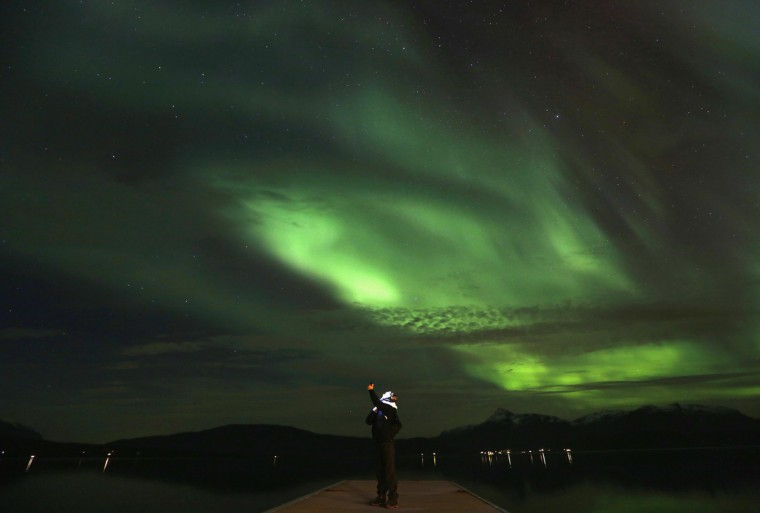 A tourist takes photos of an Aurora Borealis display (Northern Lights) over the Bals-Fiord north of the Arctic Circle, near the village of Mestervik late September 30, 2014. (Yannis Behrakis/Reuters)