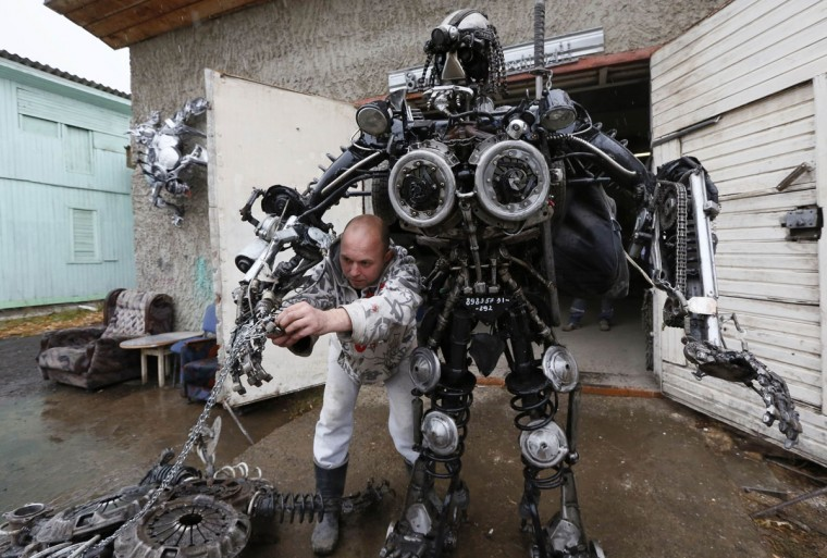 """Mechanic and welder Sergei Kulagin, 32, tests the """"Alien Samurai"""", an electro-mechanical mobile robot made by Kulagin using car components, outside an automobile repair workshop in the town of Divnogorsk outside Krasnoyarsk, Siberia, October 15, 2014. Enthusiast Kulagin, who works as a mechanic of an automobile service station, created about twenty sculptures made of used car parts and components during his non-working hours. (REUTERS/Ilya Naymushin)"""