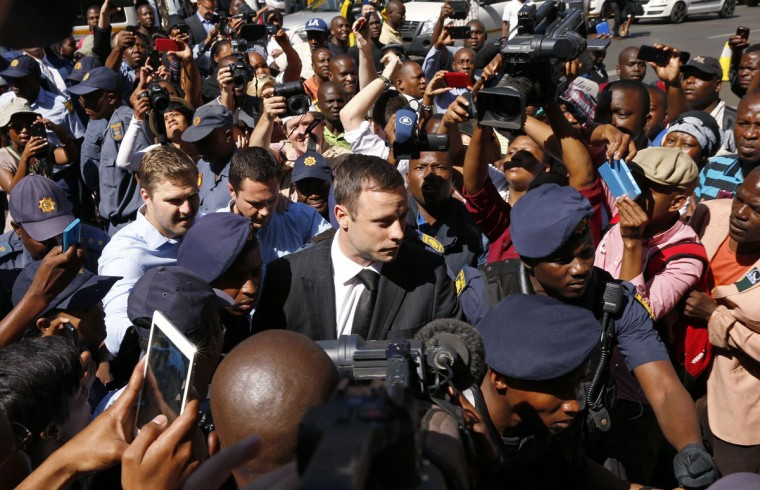 South African Olympic and Paralympic sprinter Oscar Pistorius (C) arrives for his sentencing at the North Gauteng High Court in Pretoria October 21, 2014. A judge will pass sentence on athlete Pistorius on Tuesday for killing his girlfriend, Reeva Steenkamp, after one of the most sensational murder trials in South Africa's history - and the decision could fuel controversy over the state of the country's justice system. (REUTERS/Siphiwe Sibeko)