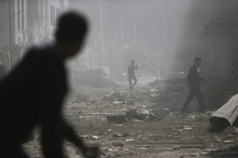 Men walk on the rubble of damaged buildings at a site hit by what activists said were air strikes by forces of Syria's President Bashar al-Assad in the Duma neighbourhood of Damascus October 20, 2014. (REUTERS/Bassam Khabieh)