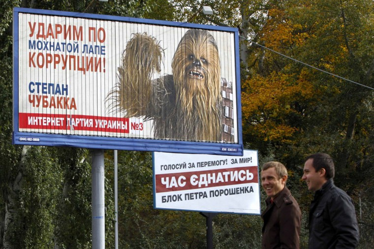 Men walk past a pre-election poster with a portrait of a candidate from the Internet party of Ukraine, Stepan Chewbacca, in the centre of Kiev October 21, 2014. Ukrainians will take part in an early parliamentary election on October 26. (REUTERS/Valentyn Ogirenko)
