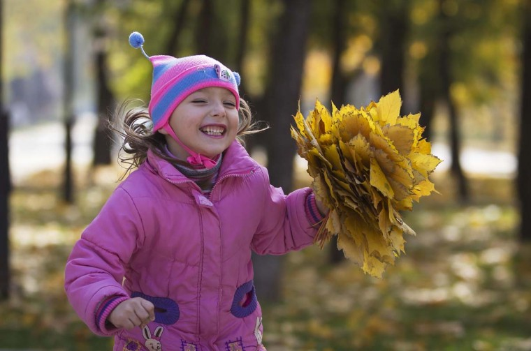 A girl runs with collected autumn leaves at a park in Donetsk, eastern Ukraine, October 17.   || PHOTO CREDIT: SHAMIL ZHUMATOV   - REUTERS