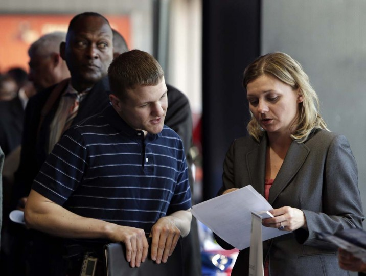 Legal firm Hogan Lovells representative Nina LeClair (R) talks to U.S. military veteran applicant Jacob Wilkens (L) at a hiring fair for veteran job seekers and military spouses at the Verizon Center in Washington in this April 9 file photo. U.S. Employers stepped up hiring in September and the jobless rate fell to a six-year low, which could bolster bets on a Federal Reserve rate hike in mid-2015 or even earlier. || PHOTO CREDIT: GARY CAMERON/FILES   - REUTERS