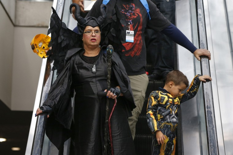 Costumed attendees ride an escalator inside New York's Comic-Con convention. The event draws thousands of costumed fans, panels of pop culture luminaries and features a sprawling floor of vendors in a space equivalent to more than three football fields in Javits Center. Shannon Stapleton/Reuters photo
