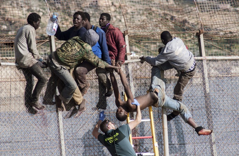 An African migrant is lowered down from a border fence by a Spanish Civil Guard as fellow migrants assist, at the border between Morocco and Spain's north African enclave of Melilla during the latest attempt to cross into Spanish territory on April 3, 2014. (REUTERS/Jesus Blasco de Avellaneda)