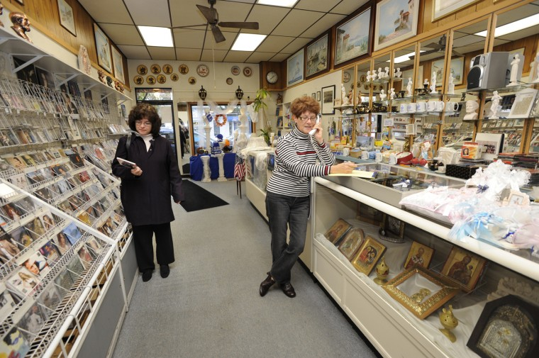 11/4/10 - Tina Bilis, in the midst of arranging to purchase gifts for her godchild's christening, looks at a CD while the owner of Kentrikon, Nitsa Morekas, takes a phone call. (Jed Kirschbaum, Baltimore Sun)