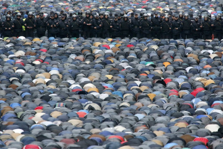 Russian Interior Ministry members stand guard as Muslims attend an Eid al-Adha mass prayer in Moscow. Muslims around the world celebrate Eid al-Adha to mark the end of the haj pilgrimage by slaughtering sheep, goats, camels and cows to commemorate Prophet Abraham's willingness to sacrifice his son, Ismail, on God's command. (Sergei Karpukhin/Reuters)