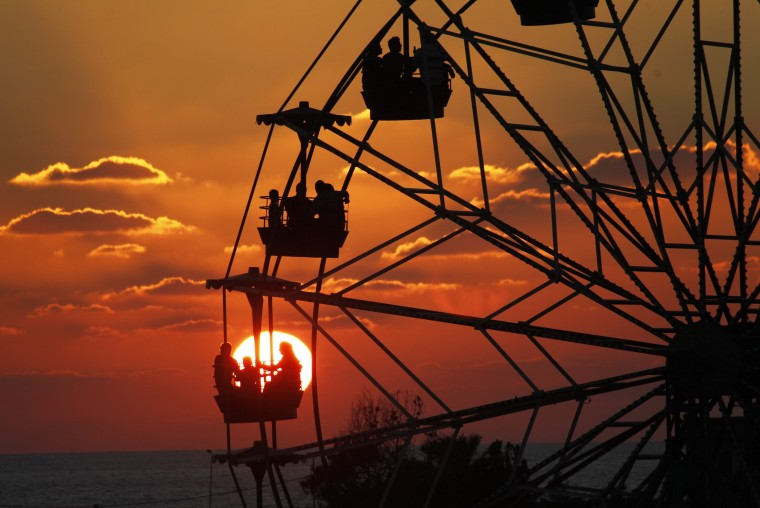 People ride a Ferris wheel in an amusement park as they celebrate the first day of Eid al-Adha, at the port-city of Sidon, southern Lebanon. (Aali Hashisho/Reuters)
