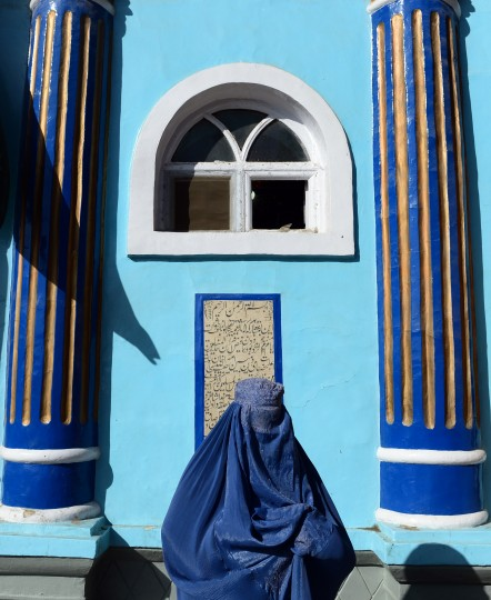 A burqa clad-Afghan woman walks through the courtyard of Shah-e Do Shamshira shrine during the Eid al-Adha festival in Kabul. The festival of sacrifice is celebrated throughout the Muslim world as a commemoration of Abraham's willingness to sacrifice his son for God with cows, camels, goats and sheep traditionally slaughtered on the holiest day. (Wakil Kohsar/AFP-Getty Images)