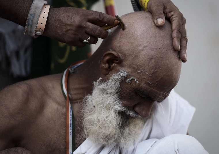 """Muslim pilgrims shave their hair after throwing pebbles at pillars during the """"Jamarat"""" ritual, the stoning of Satan, in Mina near the holy city of Mecca. Pilgrims pelt pillars symbolizing the devil with pebbles to show their defiance on the third day of the hajj as Muslims worldwide mark the Eid al-Adha or the Feast of the Sacrifice, marking the end of the hajj pilgrimage to Mecca and commemorating Abraham's willingness to sacrifice his son Ismail on God's command in the holy city of Mecca. (Mohammed Al-Shaikh/AFP-Getty Images)"""