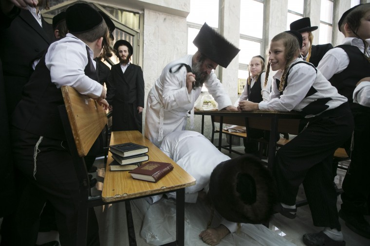 """An Ultra-Orthodox Jewish man uses a belt to hit another during """"Malkot"""" or Flagellation ritual to atone for his sins for the Yom Kippur in a synagogue in the town of Beit Shemesh, near Jerusalem, ahead of Yom Kippur, the Jewish Day of Atonement, which starts at sundown Friday. (Baz Ratner/Reuters)"""