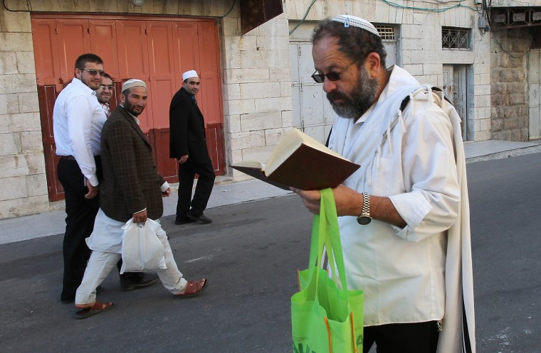 Palestinian Muslim worshipers (L) walk past a Jewish worshiper near the al-Ibrahimi mosque, or the Tomb of the Patriarch, a religious site to both Muslims and Jews, in the divided West Bank town of Hebron. The Jewish fast of Yom Kippur is coinciding with the Muslim festival of Eid al-Adha for the first time in three decades. The concurrence of the holy days has not occurred for 33 years because the two faiths use different lunar calendars. (Hazem Bader/AFP-Getty Images)